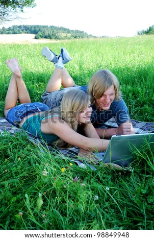 young couple with laptop outdoors in summer - stock photo