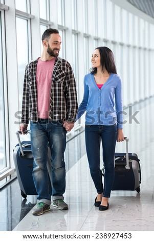 Young couple with luggage bags at airport are ready to flight.