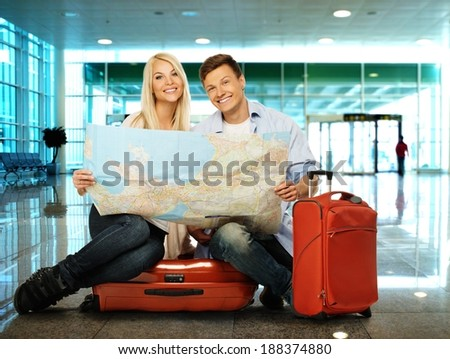 Young couple with map sitting on suitcases in airport - stock photo