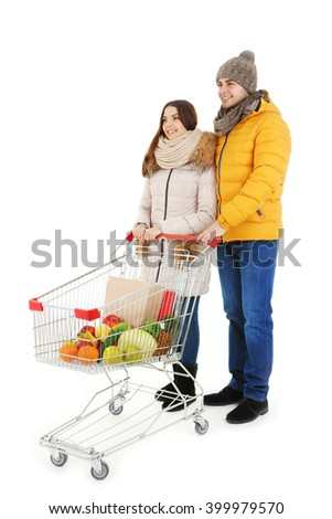 Young couple with metal trolley of products isolated on white