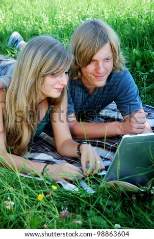 young couple with notebook outdoors in summer - stock photo