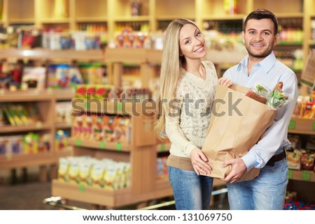 Young couple with package of products in store