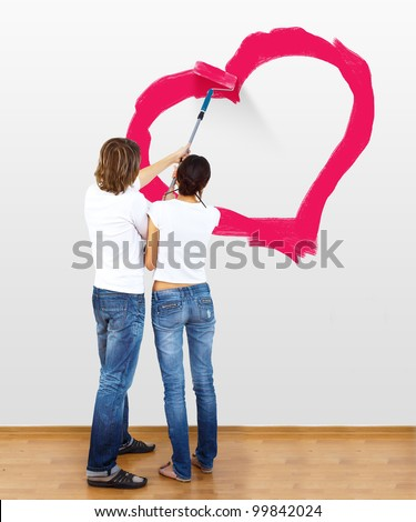 Young couple with paint brushes drawing heart on the wall - stock photo