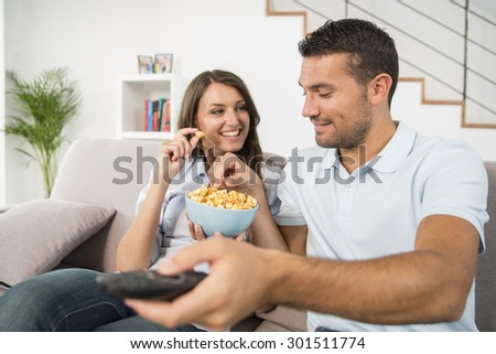Young couple with popcorn watching movie at home
