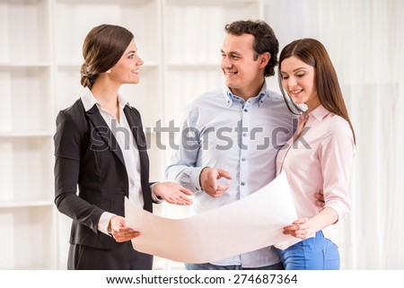 Young couple with realtor are watching the plan of a house. - stock photo