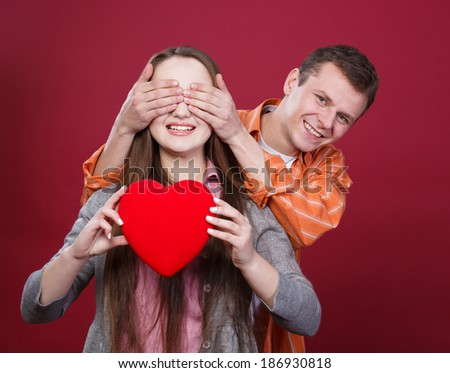 young couple with red  heart, boy close girl's  eyes with hands - stock photo