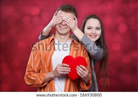young couple with red  heart, girl close boy's  eyes with hands - stock photo