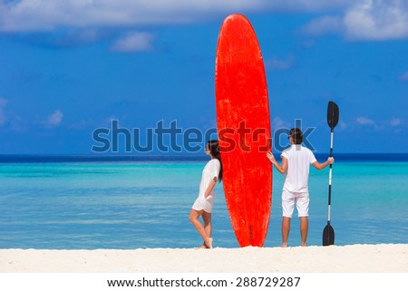 Young couple with red surfboard on white beach
