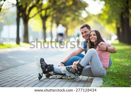 Young couple with rollers in park - stock photo