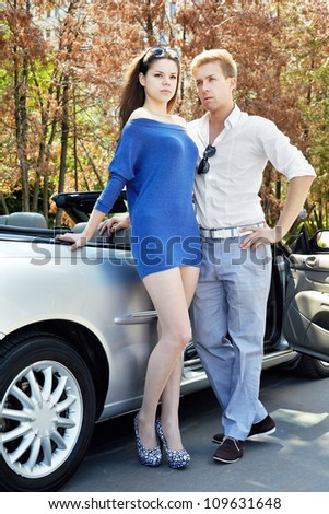 Young couple with serious faces stands near a cabriolet - stock photo