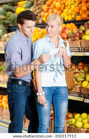 Young couple with shopping list against the piles of fruits decides what to buy