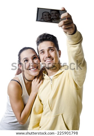 Young couple with smart phone taking selfie smiling isolated on white background - stock photo