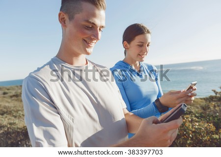 Young couple with smartphones outdoors