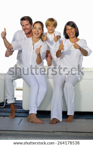 Young couple with son and grandmother  sitting in a white living room and gesturing thumbs up. Vertical. - stock photo