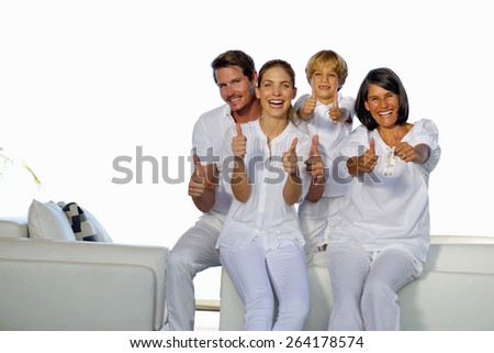 Young couple with son and grandmother  sitting in a white living room and gesturing thumbs up. Horizontal. - stock photo