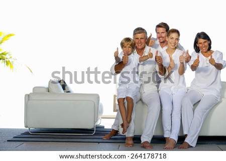 Young couple with son and grandparents  sitting in a white living room and gesturing thumbs up. Horizontal. - stock photo