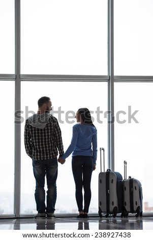 Young couple with suitcases are looking through airport window while waiting for flight. Back view. - stock photo