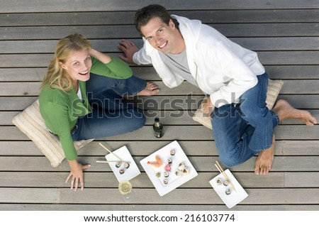 Young couple with sushi and drinks on decking, smiling, portrait, elevated view - stock photo