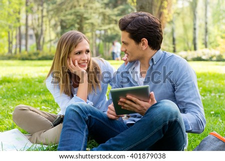 Young couple with tablet computer in the park