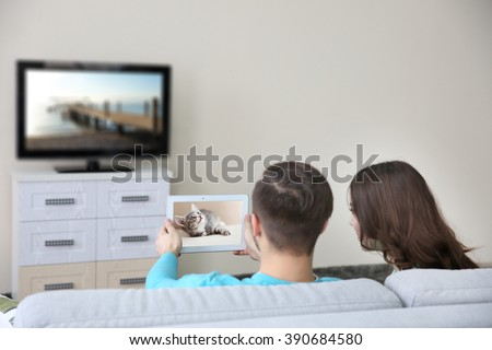 Young couple with tablet watching and taking video from the TV at home - stock photo