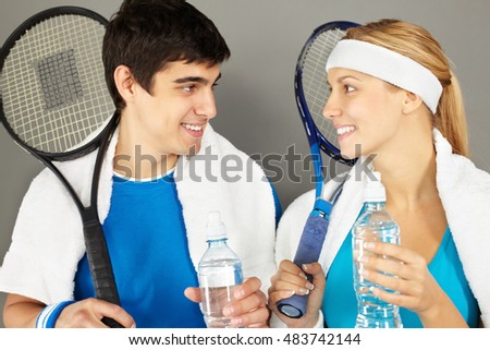 Young couple with tennis rackets drinking water, looking at each other and smiling