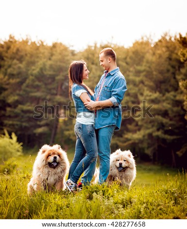 Young couple with the dogs in the park. Sunset