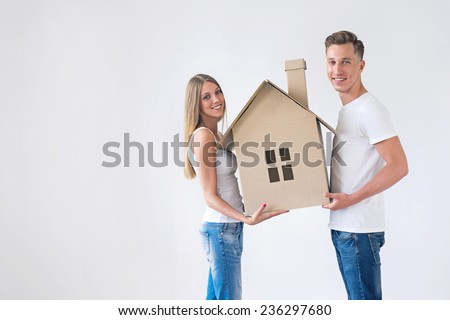 Young couple with the house of cardboard - stock photo