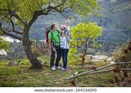 Young couple with toddler boy standing under tree in spring - stock photo