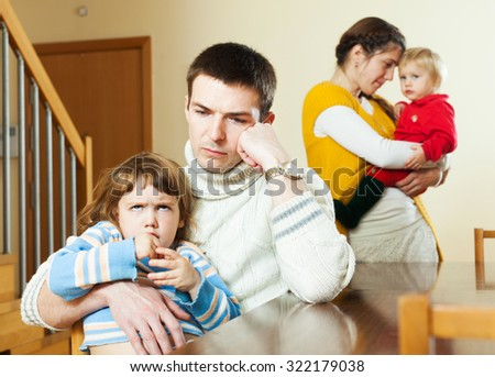 Young couple with two children in quarrel at home - stock photo
