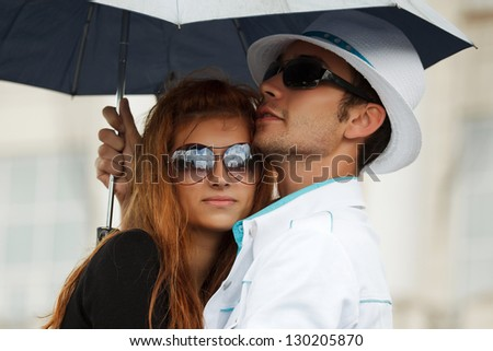 Young couple with umbrella in the rain - stock photo
