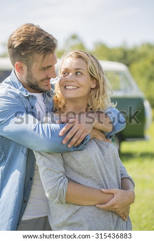 young couple with vintage camper van