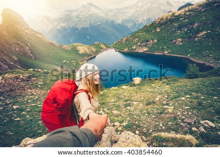 Young couple Woman with backpack holding Man hand following Travel hiking Lifestyle and relationship concept lake and mountains landscape on background - stock photo