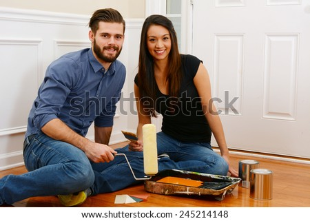 Young couple working on painting their home together - stock photo