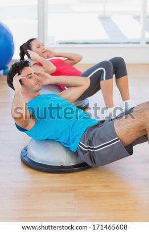 Young couple working out on dome balance in a bright gym - stock photo