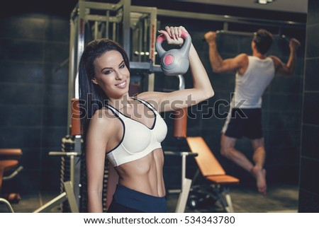 Young couple workout in gym, woman posing with kettlebell, man doing pull ups