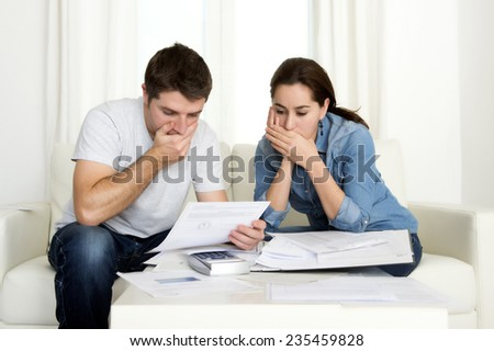 young couple worried home in stress sitting at living room couch accounting debt bills bank papers expenses and payments feeling desperate in bad financial situation