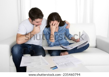 young couple worried home in stress sitting at living room couch accounting debt bills bank papers expenses and payments feeling desperate in bad financial situation - stock photo