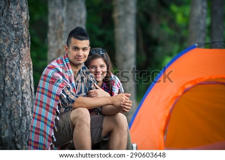 Young couple wrapped in blanket warming up in front of the tent while camping in nature - stock photo
