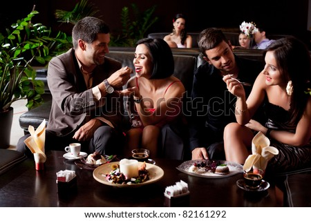 young couples eating deserts feeding each other - stock photo