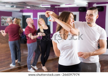 Young couples enjoying of partner dance and smiling indoor - stock photo