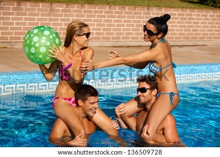 Young couples having fun on summer holiday in swimming pool, laughing. - stock photo