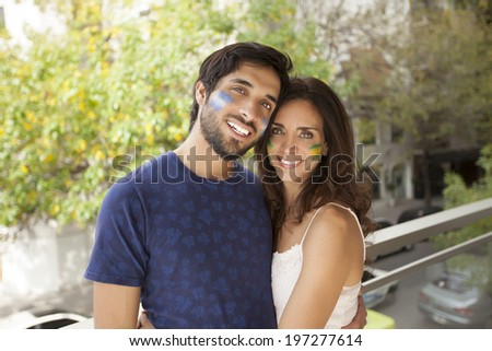 Young couples with flags painted on their cheeks - stock photo