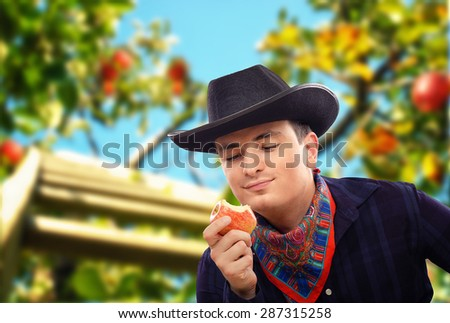 Young cowboy has picked red apple in farm and eats it. He is enjoying its taste. Guy is wearing black cowboy hat and dark blue plaid shirt. There are apple branches out of focus in background - stock photo