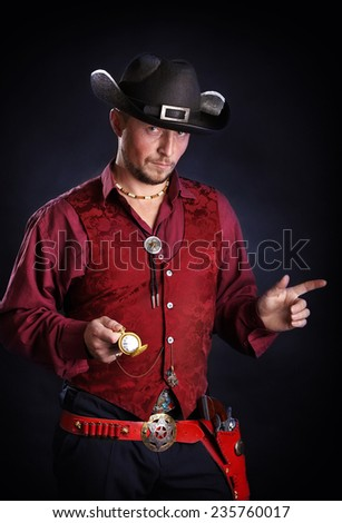 young cowboy in traditional dress holding clock