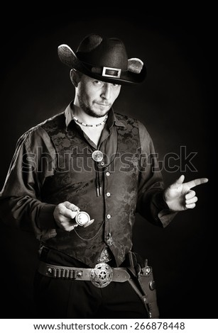 young cowboy in traditional dress holding clock - stock photo