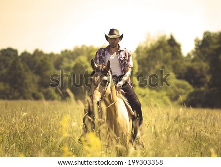 young cowboy man ridig with horse - stock photo