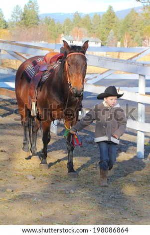 Young cowboy walking his horse on the farm - stock photo