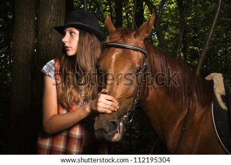 Young cowgirl in hat with bay horse - stock photo