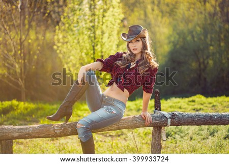 Young Cowgirl Outdoors. Sexy Fashion Model Posing in Nature - stock photo