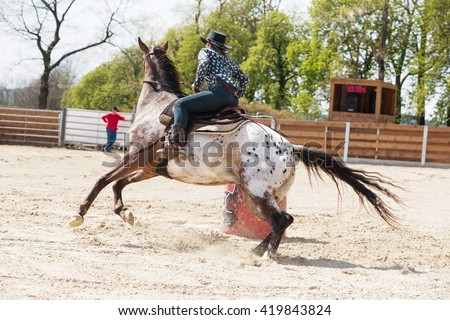 Young cowgirl riding a beautiful paint horse in a barrel racing event at a rodeo in Mitrov, Czech republic - stock photo